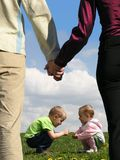 Niños en la hierba y los padres que llevan a cabo las manos Imagenes de archivo