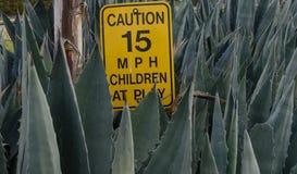 Niños en la muestra del límite de velocidad del juego Imagen de archivo libre de regalías