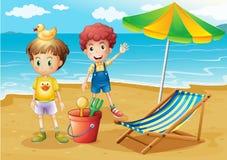 Niños en la playa con un paraguas y una cama plegable Foto de archivo libre de regalías