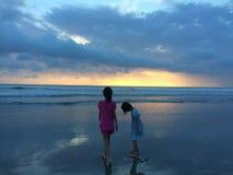 Niños en la playa de la puesta del sol Fotos de archivo