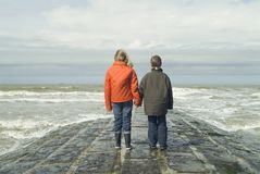 Niños en la playa, pasando por alto el mar Imagenes de archivo