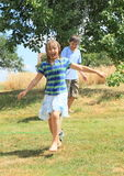 Niños en la ropa que corre a través del agua de la regadera Fotos de archivo