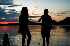 Niños en la silueta, cogida un pequeño pescado como puestas del sol a través del th Fotos de archivo