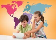 Niños en la tableta delante del mapa del mundo colorido Imágenes de archivo libres de regalías