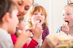 Niños en los caramelos de mordisco de la fiesta de cumpleaños Imagenes de archivo