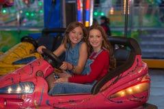 Niños en los coches de parachoques del montar a caballo de tierra justo Imagen de archivo
