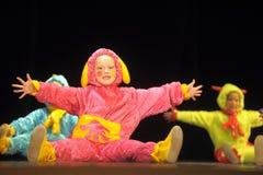 Niños en los extranjeros coloreados divertidos de los guardapolvos que bailan en etapa Fotos de archivo