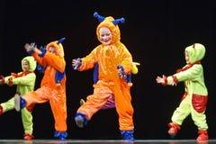 Niños en los extranjeros coloreados divertidos de los guardapolvos que bailan en etapa Foto de archivo