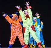 Niños en los extranjeros coloreados divertidos de los guardapolvos que bailan en etapa Fotos de archivo libres de regalías