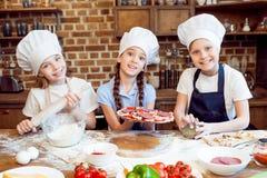 Niños en los sombreros del cocinero que hacen la pizza imagenes de archivo