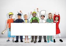Niños en los sueños Job Uniform Holding Banner Imagen de archivo libre de regalías