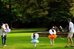 Niños en los trajes que se divierten con sus padres en el parque verde en Salzburg Fotos de archivo libres de regalías