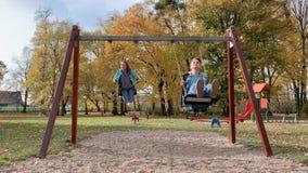 Niños en oscilaciones en el patio metrajes