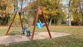 Niños en oscilaciones en el patio almacen de video