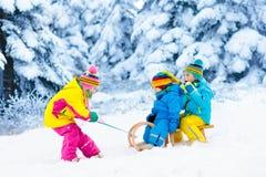 Niños en paseo del trineo Estrellazo a través de la nieve Diversión de la nieve del invierno Foto de archivo