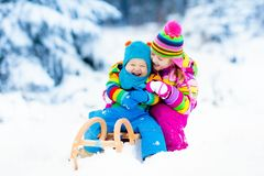 Niños en paseo del trineo Estrellazo a través de la nieve Diversión de la nieve del invierno Foto de archivo libre de regalías
