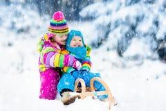 Niños en paseo del trineo Estrellazo a través de la nieve Diversión de la nieve del invierno Fotos de archivo libres de regalías