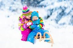Niños en paseo del trineo Estrellazo a través de la nieve Diversión de la nieve del invierno Fotografía de archivo libre de regalías
