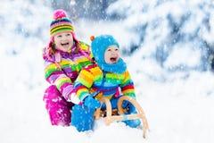 Niños en paseo del trineo Estrellazo a través de la nieve Diversión de la nieve del invierno Imagen de archivo