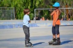 Niños en pcteres de ruedas Imagen de archivo libre de regalías