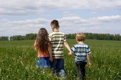 Niños en prado imagenes de archivo