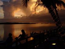 Niños en puesta del sol   Fotografía de archivo