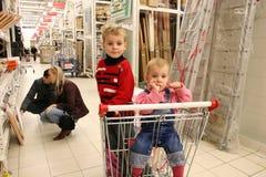 Niños en shopingcart y pares Fotos de archivo libres de regalías