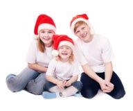 Niños en sombreros rojos de la Navidad fotografía de archivo