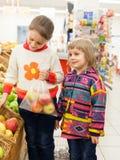 Niños en tienda con los productos Foto de archivo