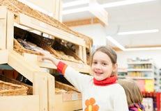 Niños en tienda en los estantes con los productos Fotos de archivo