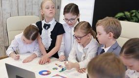 Niños en trajes en la oficina en las cartas y hablar de observación de la tabla almacen de video