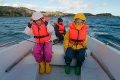 Niños en un barco flotante que lleva los chalecos de vida Fotos de archivo libres de regalías