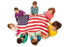 Niños en un círculo alrededor de la bandera de América Imagen de archivo libre de regalías