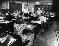 Niños en un cuarto de clase con un profesor y dos muchachos que miran uno a (todas las personas representadas no son vivas más la foto de archivo