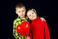 Niños en un fondo oscuro Muchacho y muchacha con el globo rojo Imágenes de archivo libres de regalías