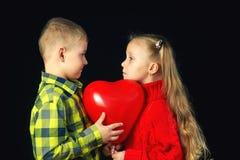 Niños en un fondo oscuro Muchacho y muchacha con el globo rojo Fotos de archivo libres de regalías