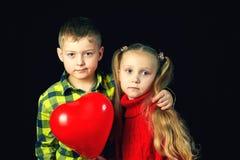 Niños en un fondo oscuro Muchacho y muchacha con el globo rojo Fotografía de archivo