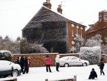 Niños en una calle que juega en nieve Fotografía de archivo libre de regalías