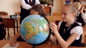 Niños en uniforme en la lección de la geografía metrajes