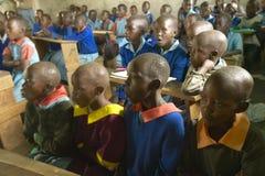 Niños en uniformes azules en la escuela detrás del escritorio cerca del parque nacional de Tsavo, Kenia, África Foto de archivo libre de regalías