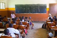 Niños en uniformes en la sala de clase de la escuela primaria listetning al profesor en zona rural cerca de Arusha, Tanzania, Áfr Foto de archivo