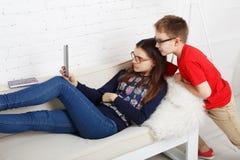 Niños en vidrios con la tableta, apego del ordenador Fotografía de archivo