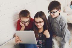 Niños en vidrios con la tableta, apego del ordenador Imágenes de archivo libres de regalías
