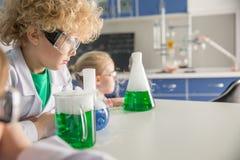 Niños en vidrios protectores y capas del laboratorio que hacen el experimento imágenes de archivo libres de regalías