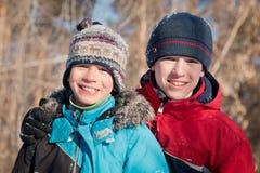 Niños en winterwear que ríen mientras que juega en nieve acumulada por la ventisca Imagen de archivo
