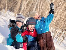 Niños en winterwear que ríen mientras que juega en nieve acumulada por la ventisca Fotos de archivo