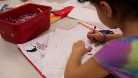 Niños escuela-envejecidos elementales que trabajan en las tablas (3 de 4) almacen de video
