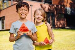 Niños exuberantes que comen una sandía madura Foto de archivo libre de regalías
