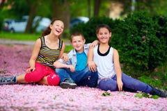 Niños felices, adolescentes que se divierten en parque floreciente Imagen de archivo
