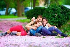 Niños felices, adolescentes que se divierten en parque floreciente Imagen de archivo libre de regalías